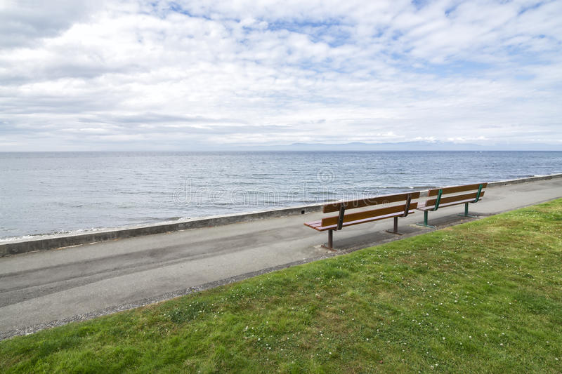 Qualicum Beach boardwalk in the summer. Qualicum Beach is a town located on Vancouver Island British Columbia,Canada.Boardwalk on a sunny summer day, cloudy sky royalty free stock images