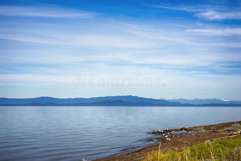 Qualicum beach in Vancouver Island, with the Canadian Rockies in. Seaside view of Qualicum beach in Vancouver Island, with the Canadian Rockies in the background stock images