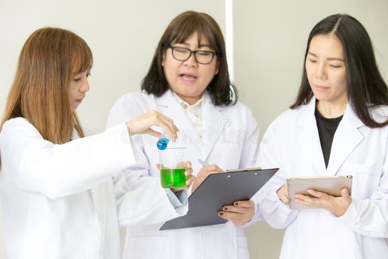 Qualidade científica dos testes do químico do teste de Sciene Cientista do grupo que trabalha no laboratório Uns homem e mulher t imagem de stock