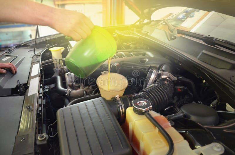 Qualidade de reabastecimento e de derramamento do óleo no carro de motor do motor fotografia de stock