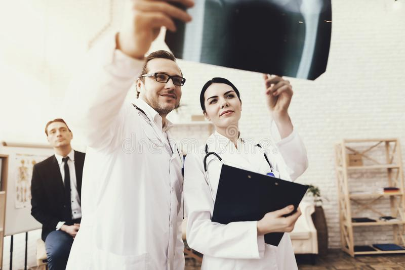 Qualified doctor with stethoscope and nurse examining x-ray of businessman at clinic. stock photo
