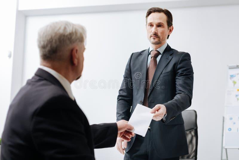 Qualifizierter Angestellter, der dem Arbeitgeber eine Entlassungsmitteilung gibt stockfotografie