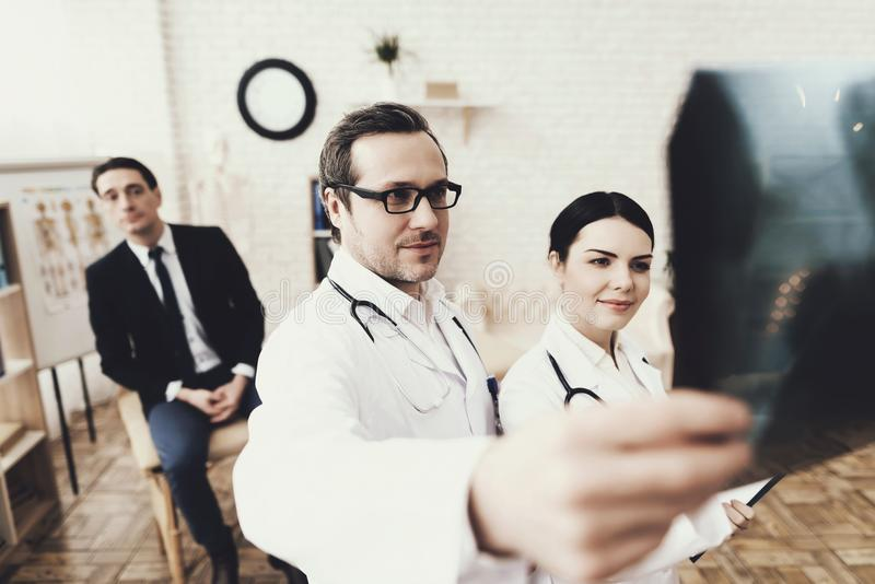 Qualifizierter Doktor mit Untersuchungsröntgenstrahl des Stethoskops und der Krankenschwester des Geschäftsmannes an der Klinik stockfoto