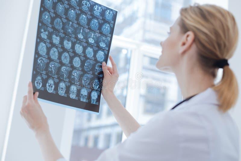 Qualifizierter medizinischer Spezialist, der Röntgenbild am Labor analysiert lizenzfreies stockbild