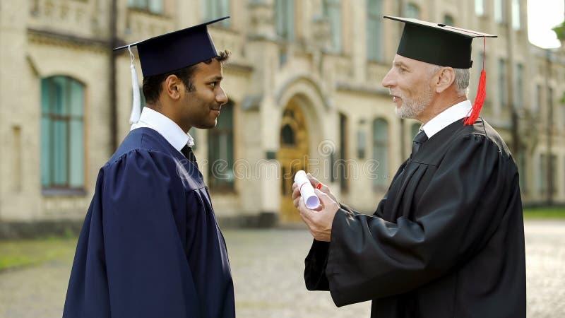 Qualifizierter Professor, der dem männlichen Studenten Diplom der Mischrasse beglückwünscht ihn gibt lizenzfreies stockfoto