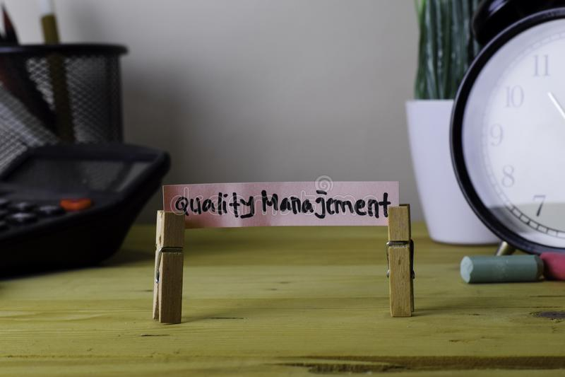 Qualità Manajement Scrittura sulle note appiccicose in mollette sulla scrivania di legno immagini stock libere da diritti