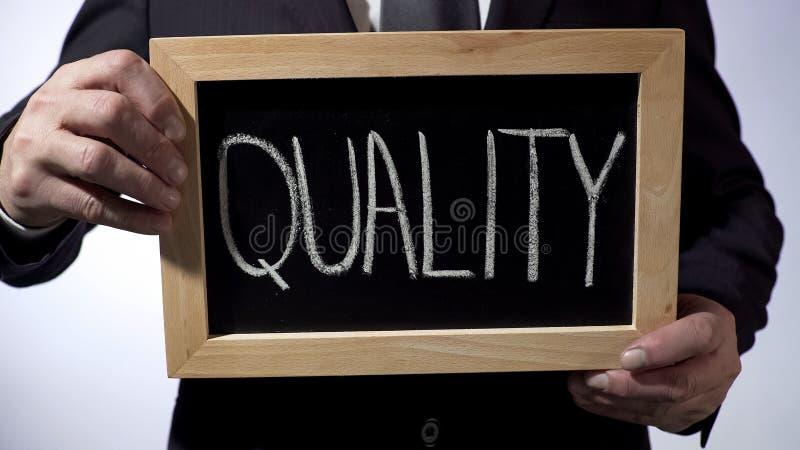 Qualità scritta sulla lavagna, segno della tenuta dell'uomo d'affari, concetto di affari immagini stock