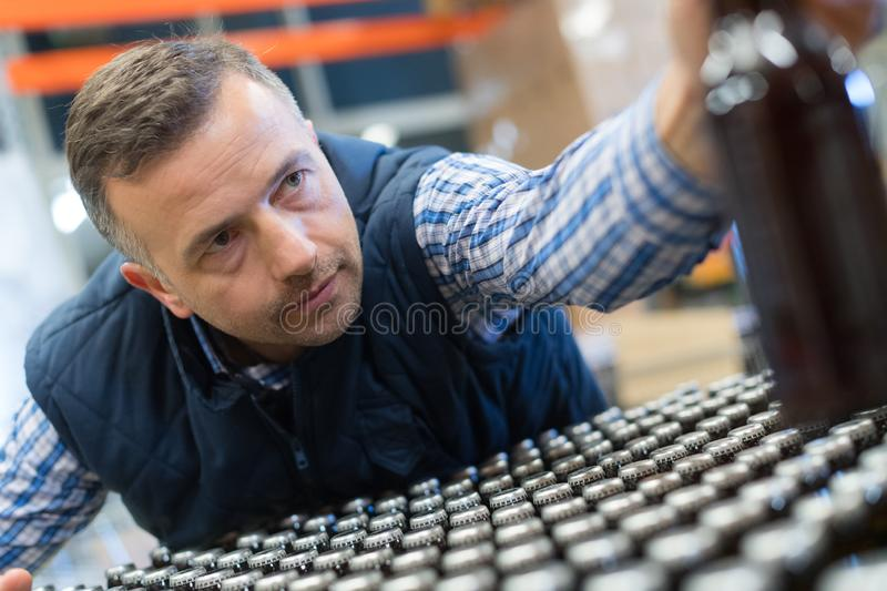 Quality control in bottling factory. Male stock photos