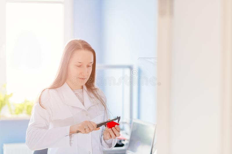 Quality control with caliper. Woman checking the dimensions of the component made in the 3d printer by caliper. Quality control stock photo