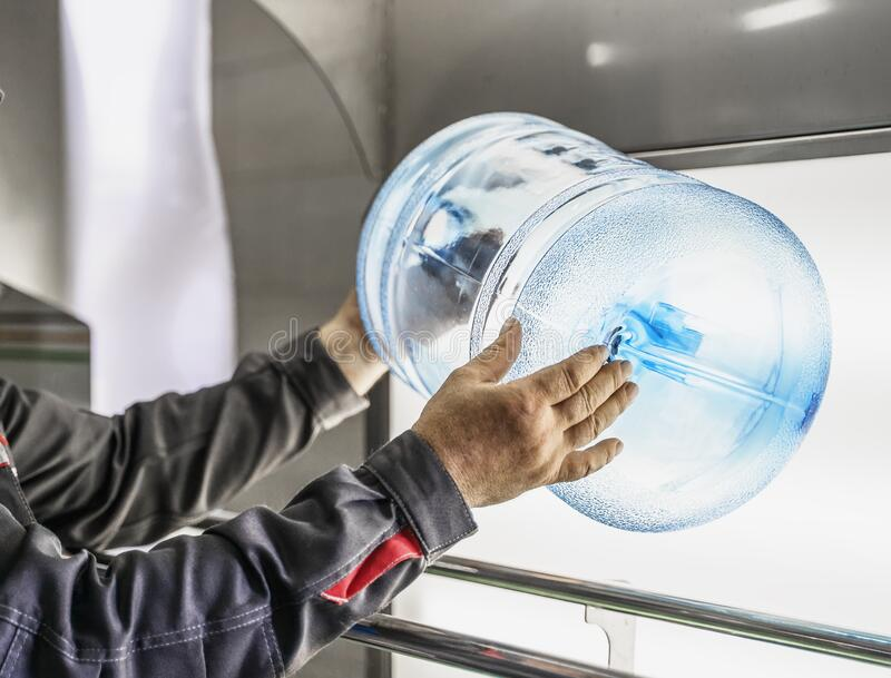 Quality control in water production factory. Plastic bottle in worker hands, crack check, close up stock photo