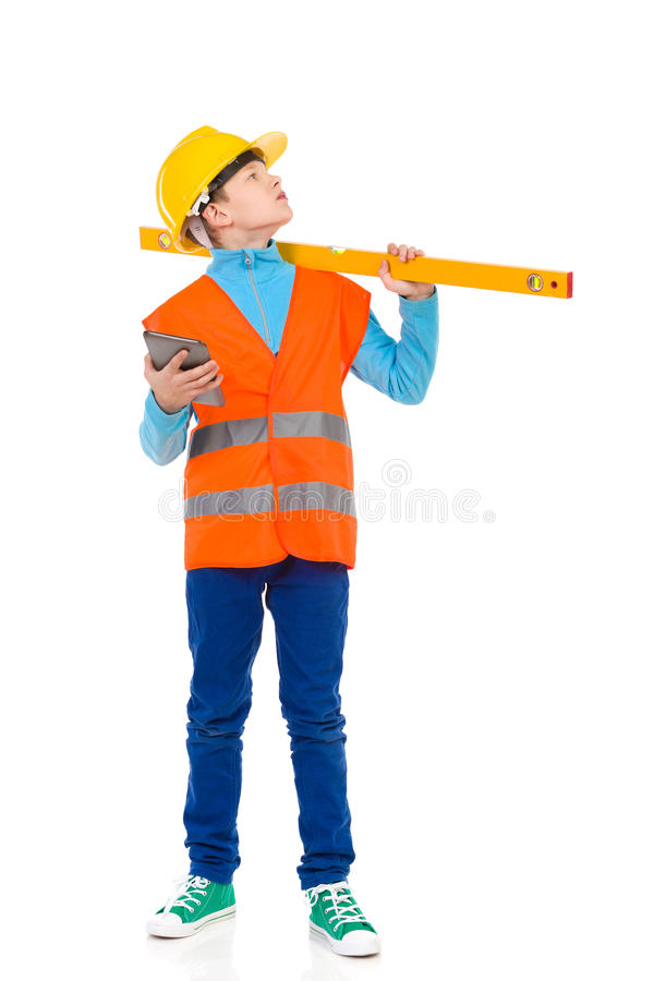 Quality control. Young boy in yellow hardhat and orange reflective vest holding a spirit level on his shoulder. Full length studio shot isolated on white stock photos