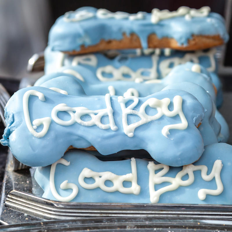 Quality Decorative Blue Dog Treats with White Words Good Boy. Display of lovely high quality decorative dog treats in bone shape with blue icing and the words royalty free stock images
