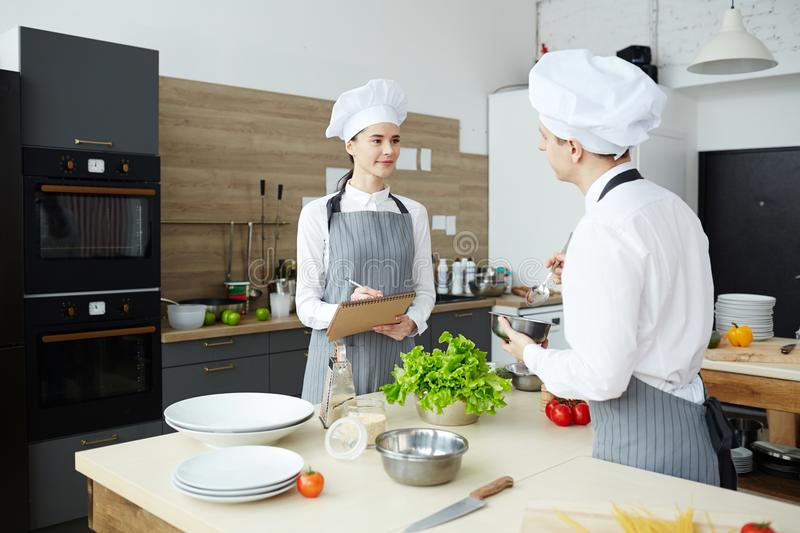 Quality expert examining commercial kitchen. Confident female quality expert in cooks uniform examining commercial kitchen and making notes in sketchpad while stock photo
