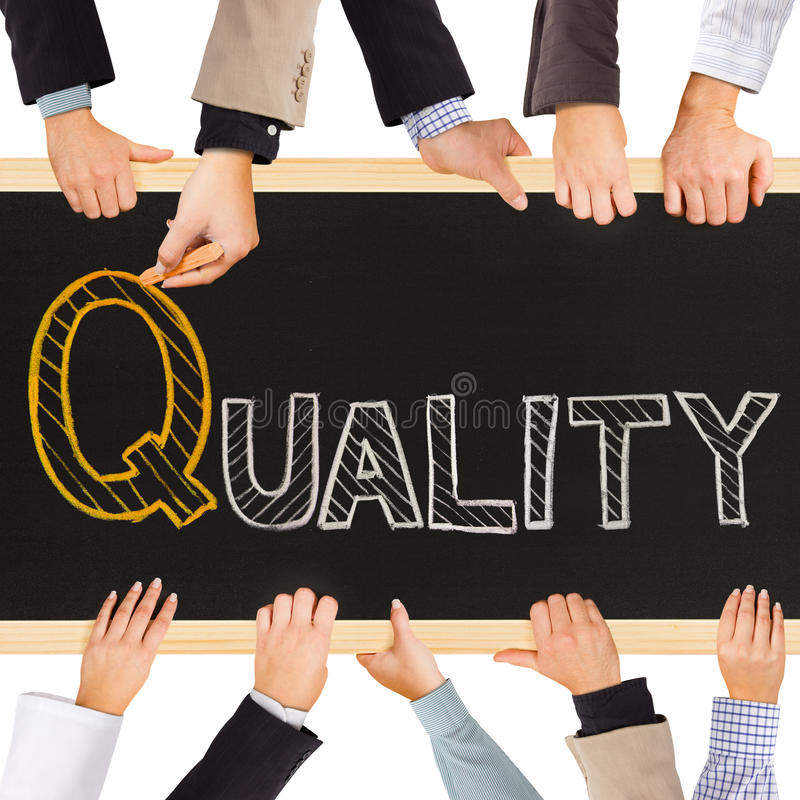 Quality. Photo of business hands holding blackboard and writing QUALITY concept stock photos