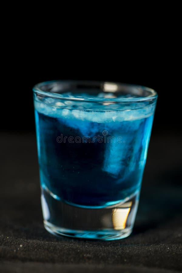 Quallen schossen Cocktail mit blauem Curaçao, sambuca, Wodka und Milch stockbilder