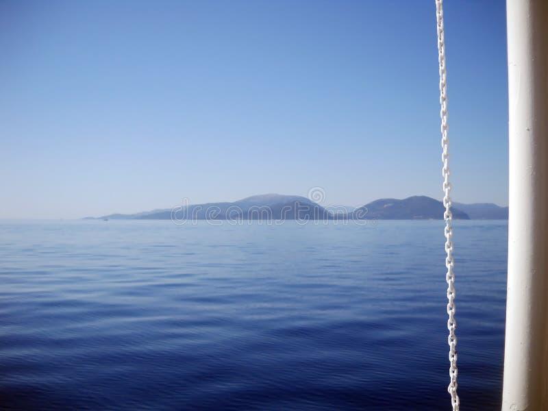 Quando il blueness di vista sul mare incontra la bianchezza della barca immagine stock