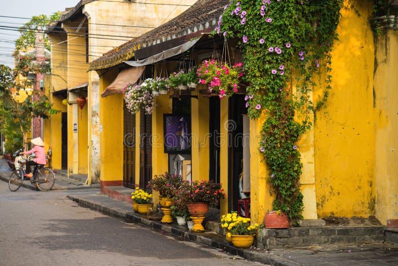Quang Nam, Vietnam - 2. April 2016: Altes gealtertes Haus mit gelben Wand- und Blumentöpfen gegen Radfahrenfrau auf Hintergrund H lizenzfreie stockbilder