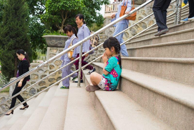 Quang Ninh, Vietnam - 22. März 2015: Verschluss des kleinen Mädchens Kinderihre Hände, die an altem Tempel Cai Baus in Van Don be stockfoto
