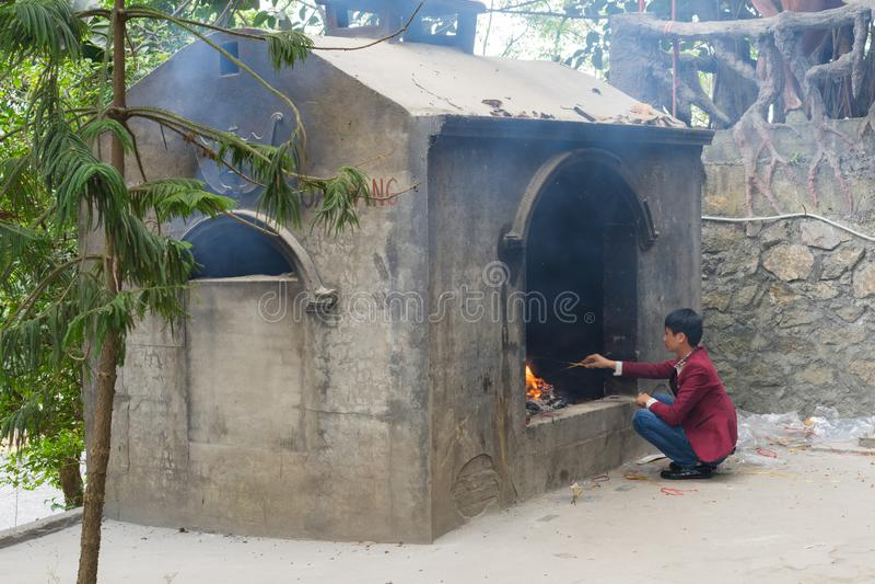 Quang Ninh, Vietnam - 22 mars 2015 : Un papier votif de brûlure d'homme au temple de Tien de chapeau, Van Don C'est culture relig photographie stock