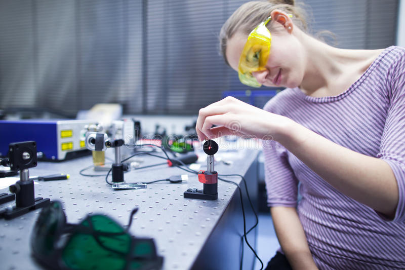 In a quantum optics lab. Female scientist doing research in a quantum optics lab (color toned image royalty free stock images