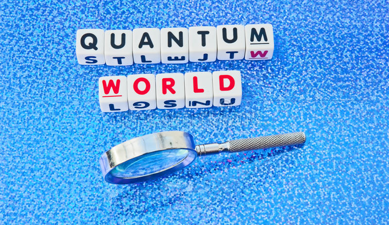 Quantum world. Text quantum world' in uppercase red and black letters on small white cubes with hand magnifier, blue dotted background. Concept of studying atoms royalty free stock photo