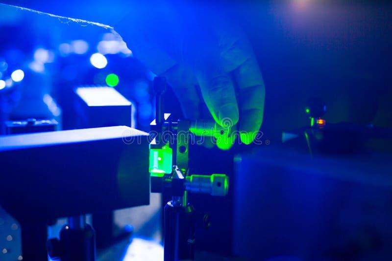 Quantumoptica - hand van een onderzoeker die een laserstraal aanpassen stock afbeelding