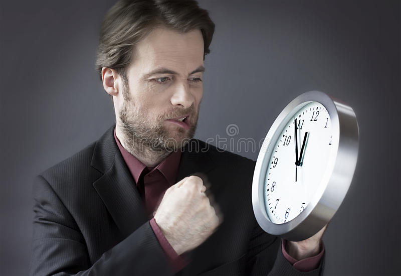 Employé de bureau sous l'horloge de poinçon de pression de temps avec son poing photo stock