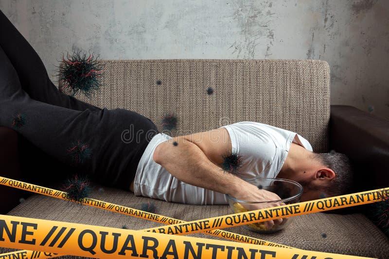 Quarantine Barrier amarelo fita proibida, isolamento Coronavírus Um homem se senta em casa sobre uma partícula isolante da COVID- foto de stock royalty free
