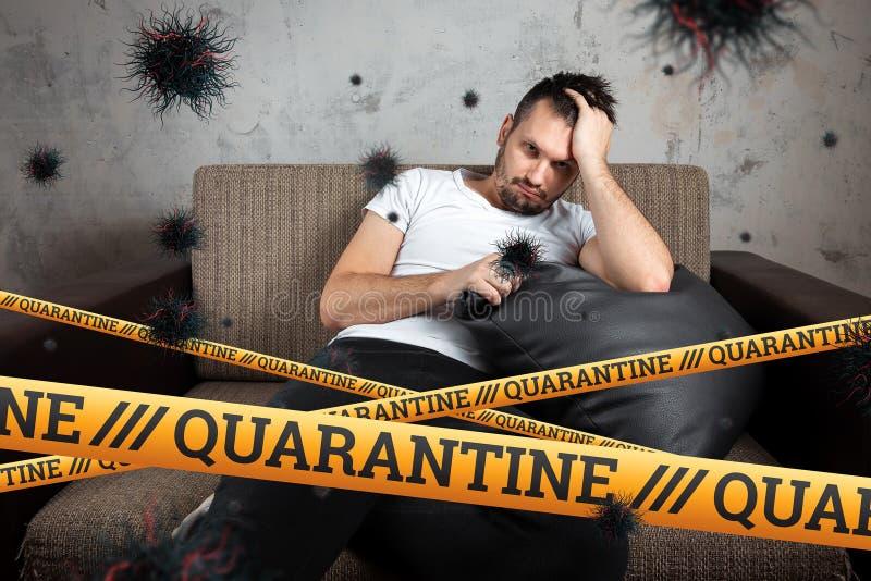 Quarantine Barrier amarelo fita proibida, isolamento Coronavírus Um homem se senta em casa sobre uma partícula isolante da COVID- imagem de stock