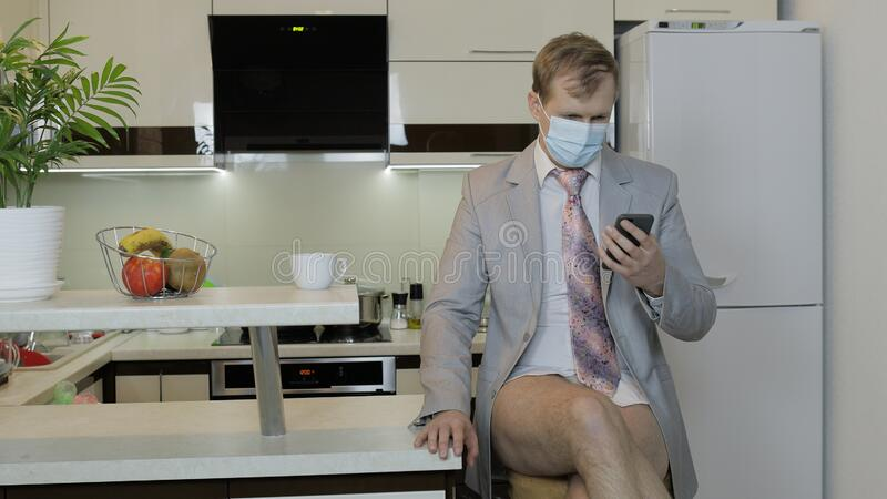 Quarantine. Businessman in mask working on phone at home office. Coronavirus. Quarantine communication. Businessman at home. Handsome man in medical mask working stock photo