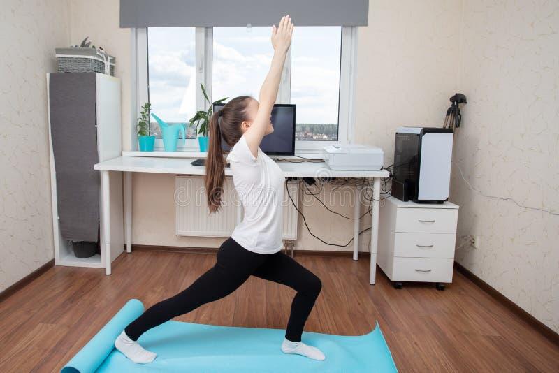 Quarantine yoga klassen Meisje doet online oefeningen via een videogesprek royalty-vrije stock foto's