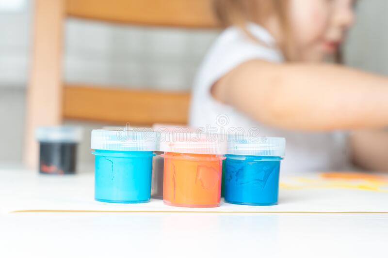 Quarantined children`s creativity due to coronavirus. Set of gouache in jars placed on a table for children`s creativity. In the background a child in blur royalty free stock photo