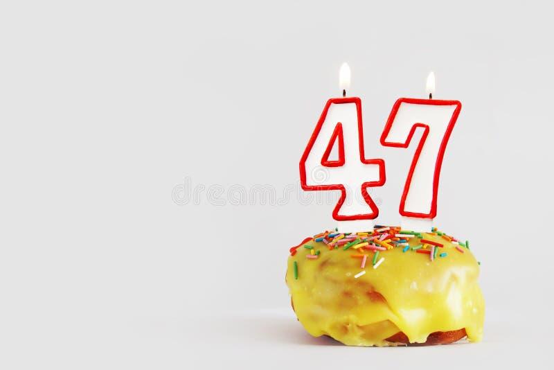 Quarenta e sete anos de aniversário Queque do aniversário com velas ardentes brancas com beira vermelha sob a forma do número qua foto de stock