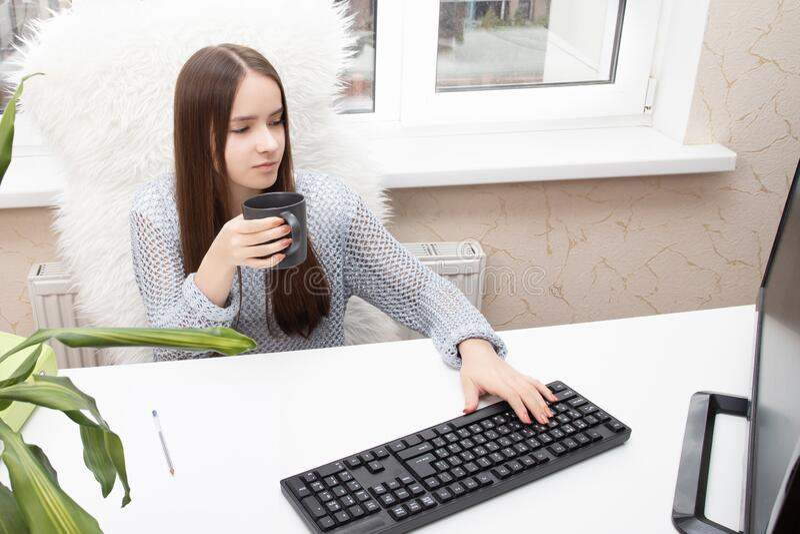 Quarentena, isolamento e trabalho remoto em casa são seguros Menina sentada em uma mesa, digitando em um computador, sorrindo imagens de stock royalty free