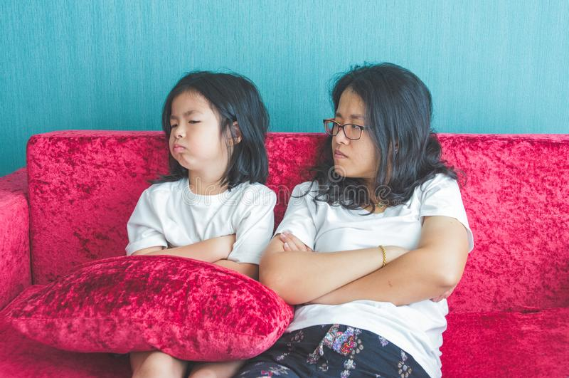 Quarrel of little daughter and mother on sofa at home royalty free stock photo