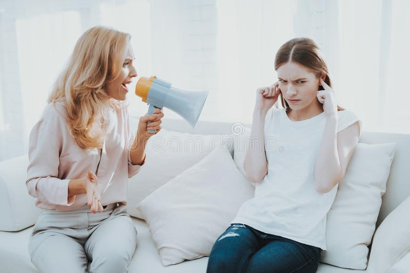 Quarrel between Mother and Daughter in White Room. Emotional Discussion. Sitting on Couch. Conflict in Family. Parent and Child. Unhappy Girl. Communication royalty free stock photography