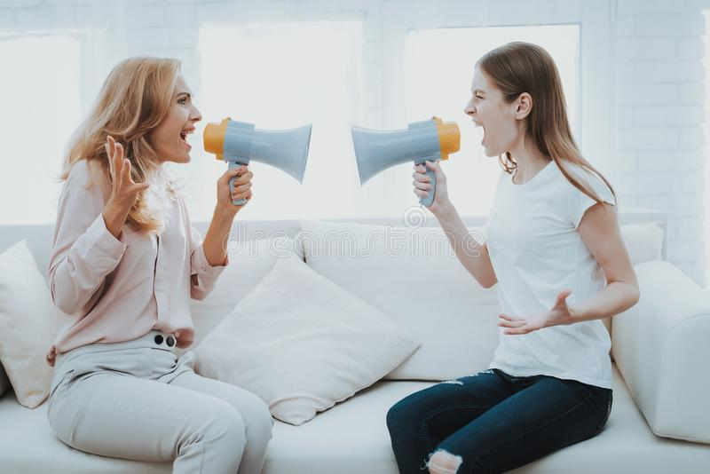 Quarrel between Mother and Daughter in White Room. Emotional Discussion. Sitting on Couch. Conflict in Family. Parent and Child. Unhappy Girl. Communication royalty free stock photo