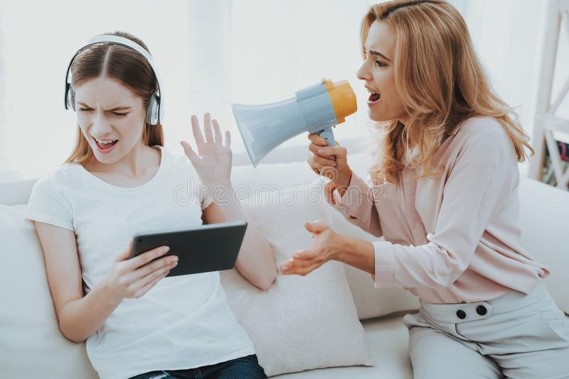 Quarrel between Mother and Daughter in White Room. Emotional Discussion. Sitting on Couch. Conflict in Family. Parent and Child. Unhappy Girl. Communication stock photo