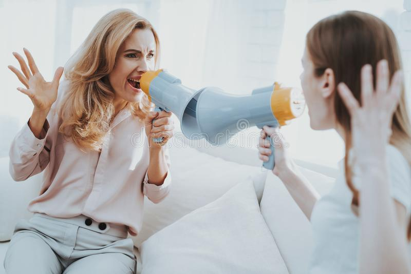 Quarrel between Mother and Daughter in White Room. Emotional Discussion. Sitting on Couch. Conflict in Family. Parent and Child. Unhappy Girl. Communication stock photography