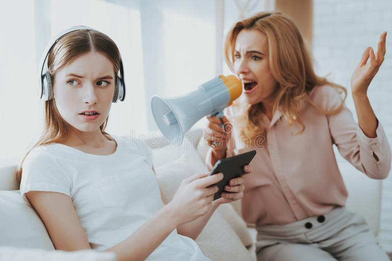 Quarrel between Mother and Daughter in White Room. Emotional Discussion. Sitting on Couch. Conflict in Family. Parent and Child. Unhappy Girl. Communication royalty free stock images