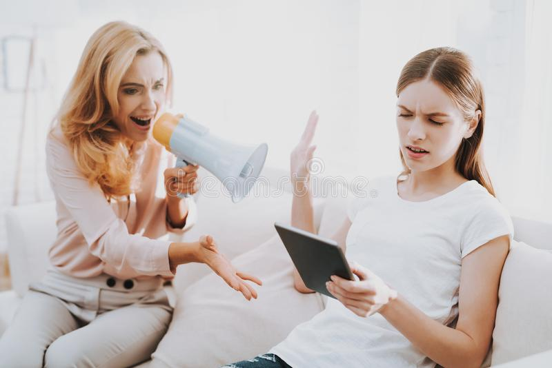 Quarrel between Mother and Daughter in White Room. Emotional Discussion. Sitting on Couch. Conflict in Family. Parent and Child. Unhappy Girl. Communication stock image
