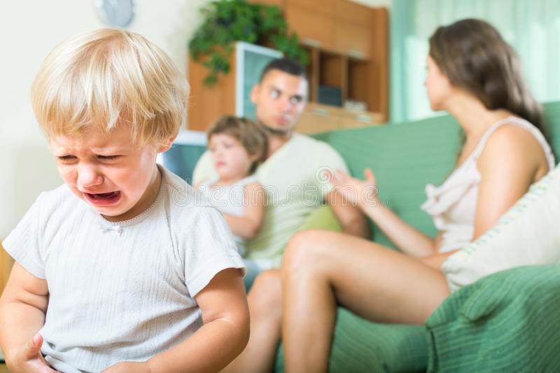 Quarrel of parents. Little child crying due to a quarrel of parents royalty free stock photo