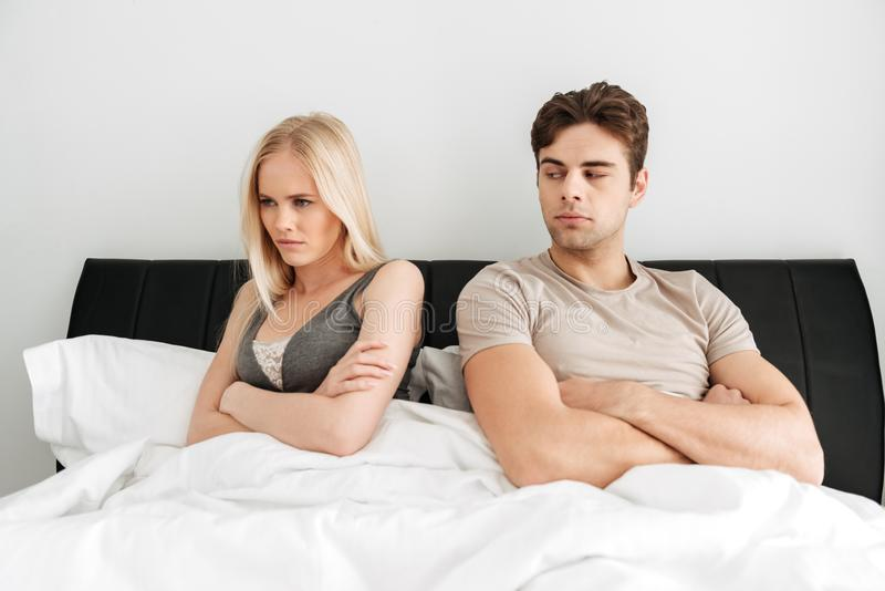 Quarreled couple sitting in bed and don`t looking at each other royalty free stock photo