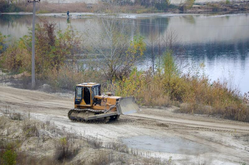 Quarry aggregate with heavy duty machinery. Caterpillar loader Excavator with backhoe driving to construction site quarry stock image