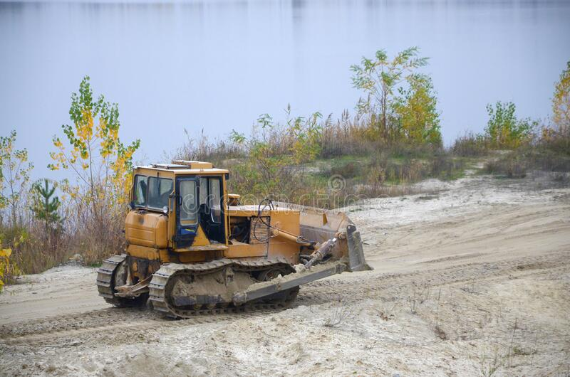 Quarry aggregate with heavy duty machinery. Caterpillar loader Excavator with backhoe driving to construction site quarry royalty free stock photos