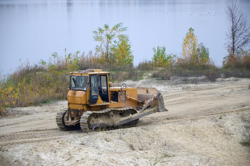 Quarry aggregate with heavy duty machinery. Caterpillar loader Excavator with backhoe driving to construction site quarry royalty free stock photo