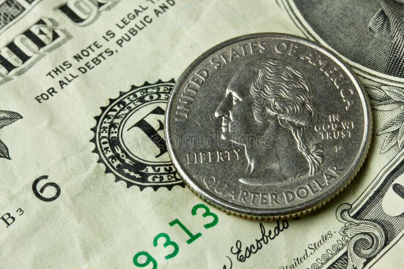 Quarter. A quarter coin on a one dollar bill stock photography
