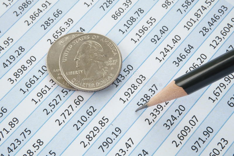Quarter Dollar coins on top of spreadsheet royalty free stock photo
