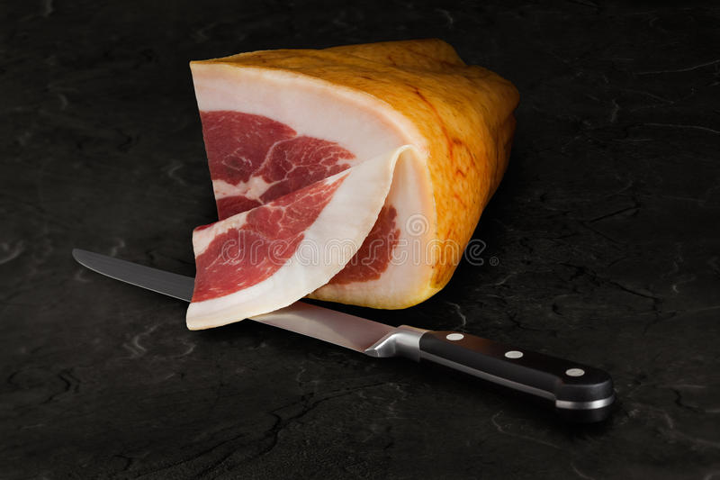 Iberico Ham. A quarter of iberico ham, mid sliced and knive on a slate plate stock photo