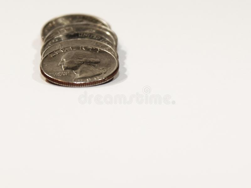 Quarter Stack Spill. Stack of American quarters spilling forward on the left side of the frame royalty free stock photo